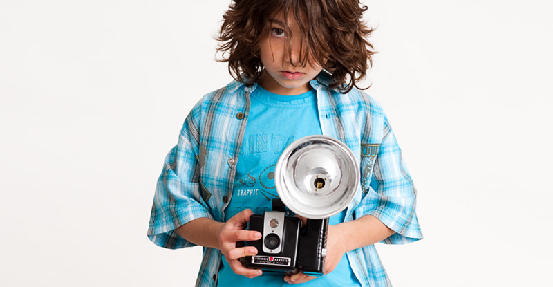 Studio portrait of young boy holding vintage film camera (Brownie Hawkeye).